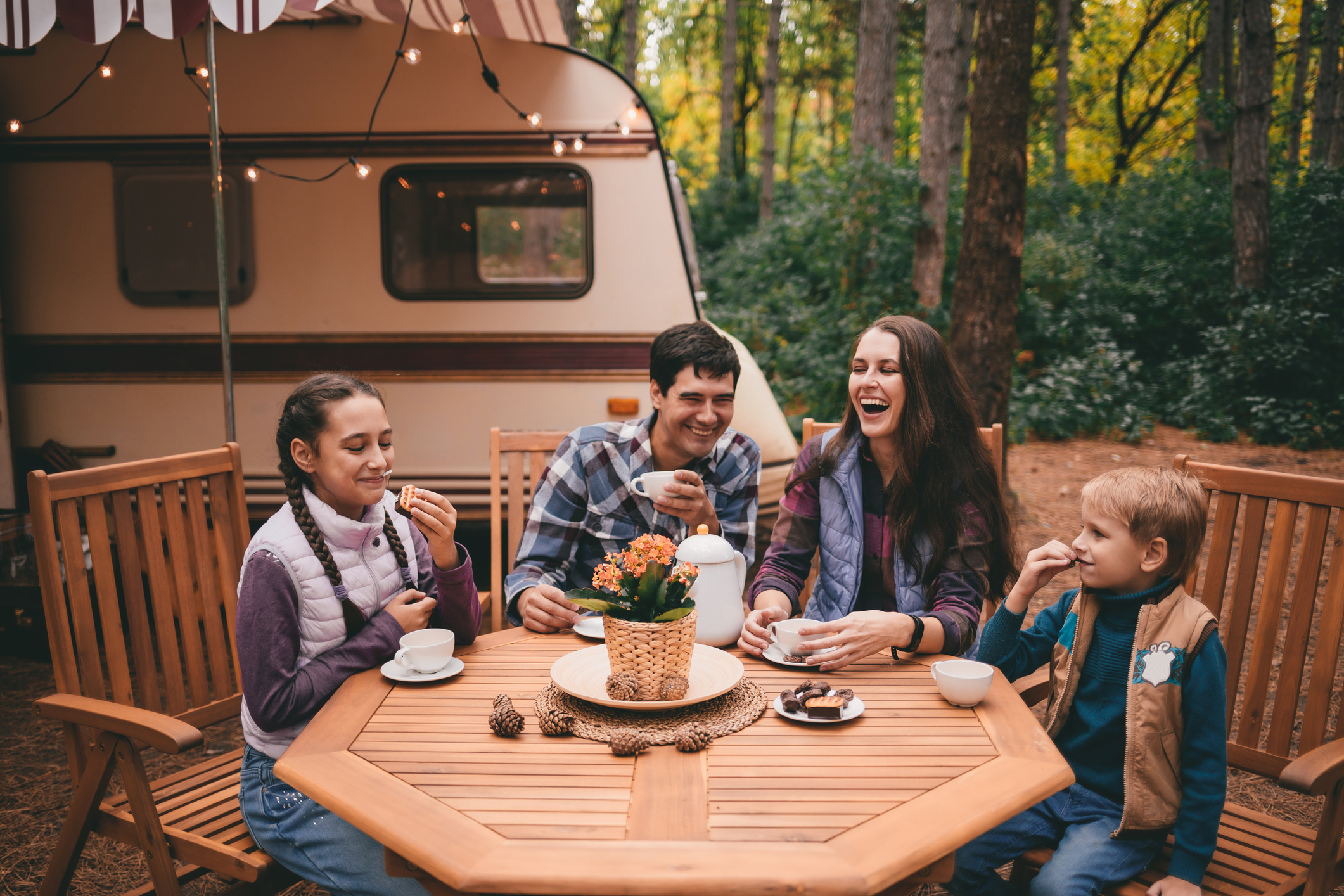 family sitting around a table outside their RV - best campgrounds in Pennsylvania