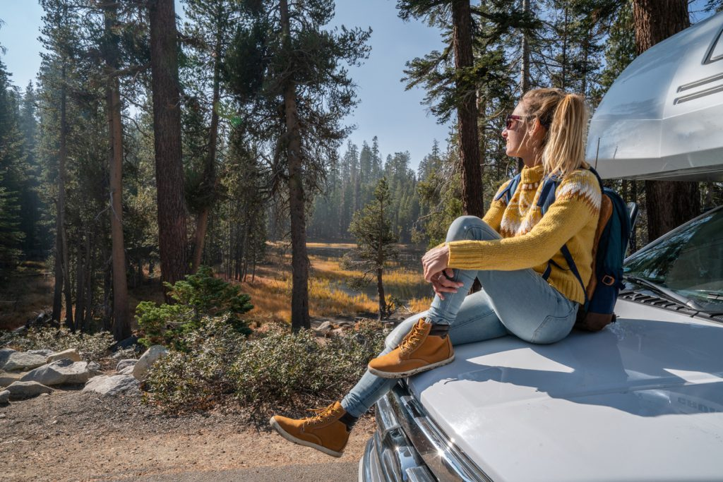 Safely Camping in the Mountains -Road trip concept; Woman driving in USA enjoying nature