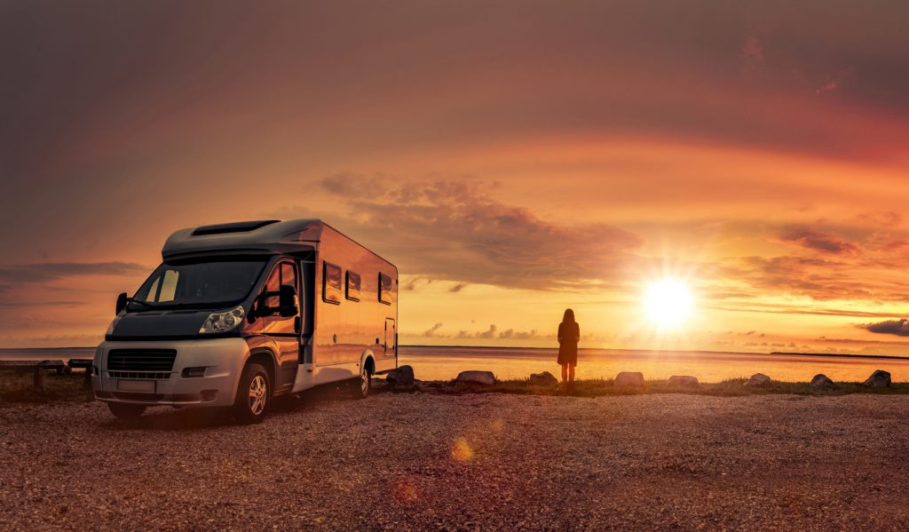 RV Types - Woman at sunset with mobile home on the beach