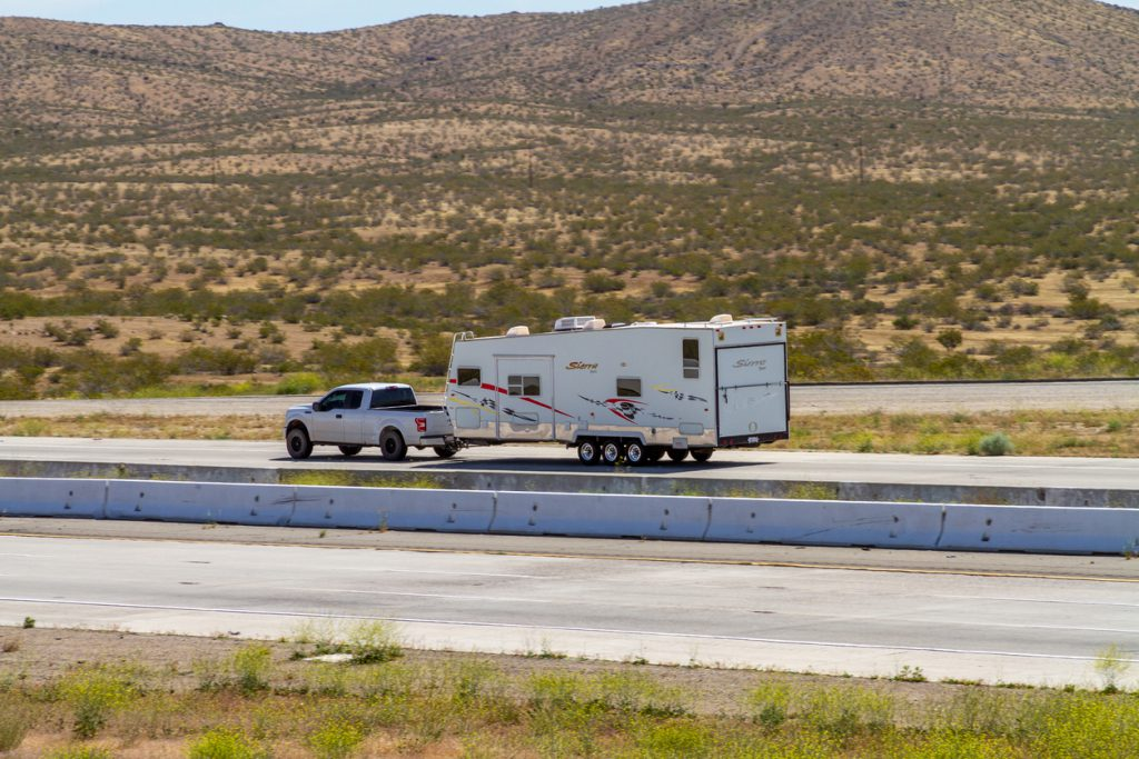 RV Types - Apple Valley, CA / USA – May 16, 2020: A truck towing a RV trailer on Interstate 15 in the Mojave Desert near the Town of Apple Valley, California.