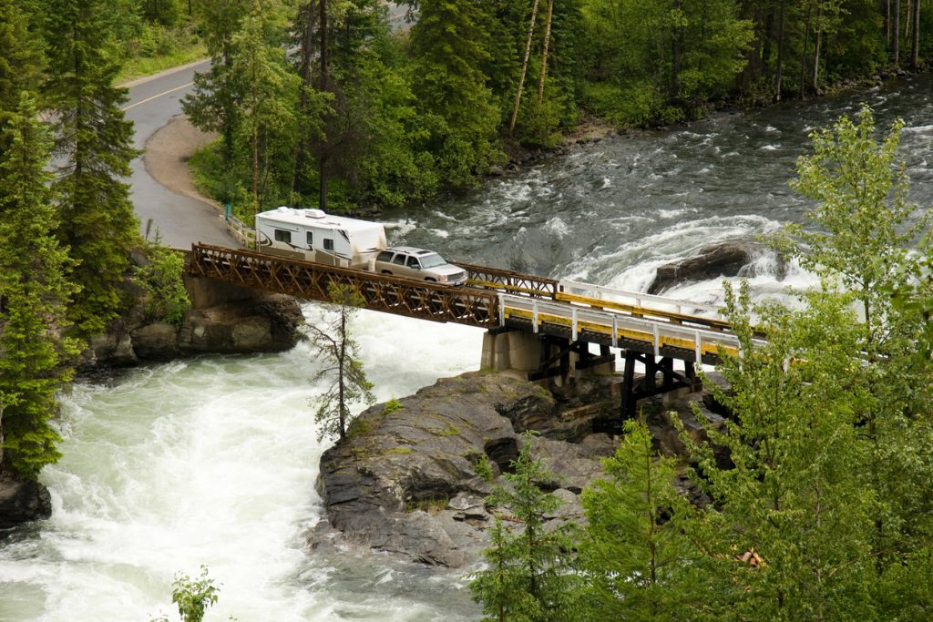 Safely Camping in the Mountains - A pickup truck and an RV trailer cross a bridge over a river