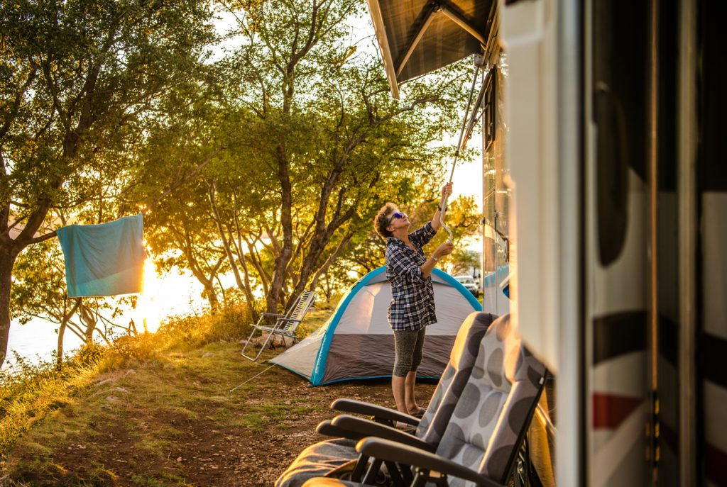 Caucasian Retired Woman in Her 60s Extending RV Awning at RV Park Campsite. Summer Vacation Time with Recreational Vehicle.