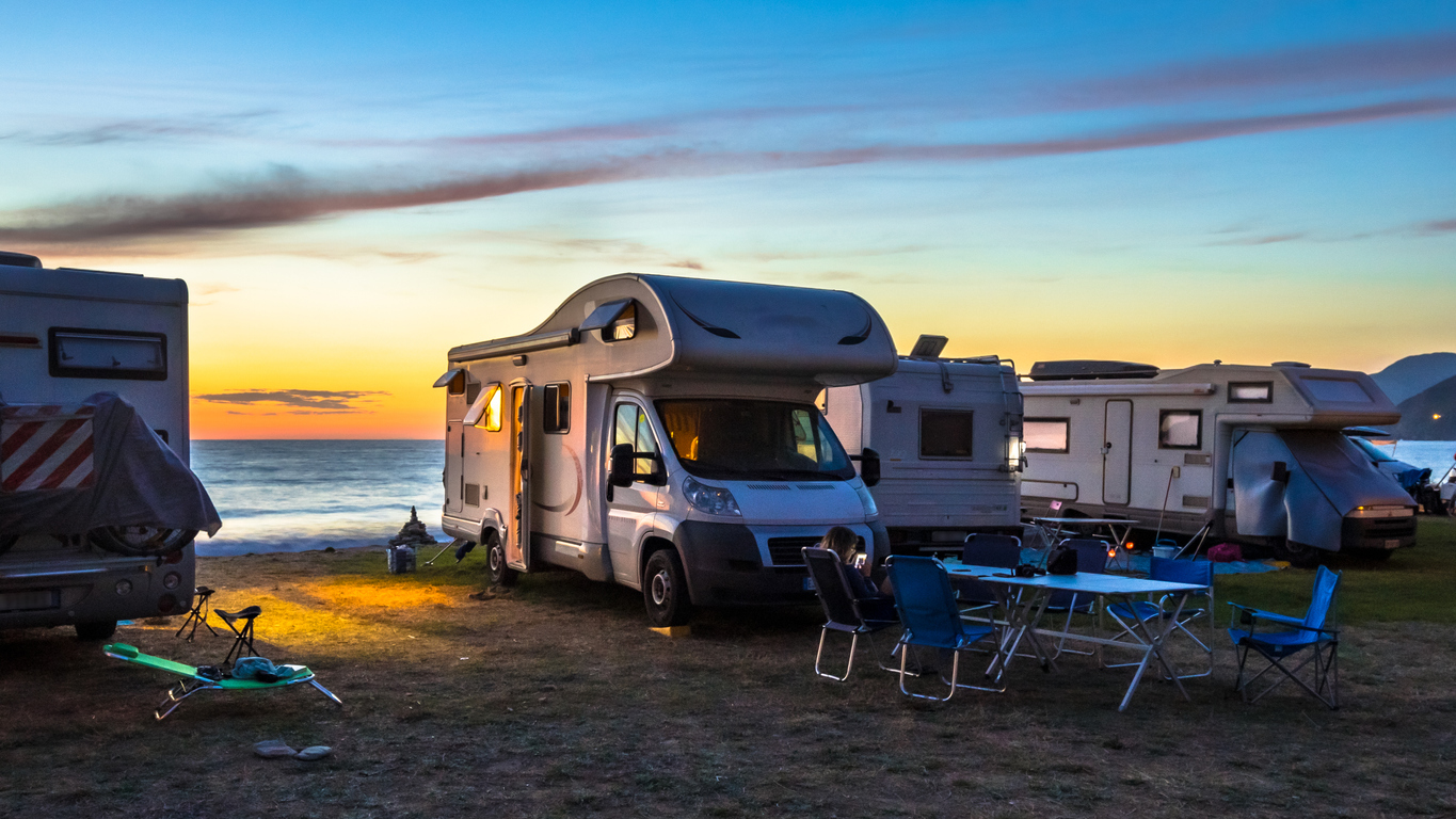 RV Security - Campers and Motorhomes overlooking sunset in the Mediterranean sea from their campsite on the beach, Corsica, France
