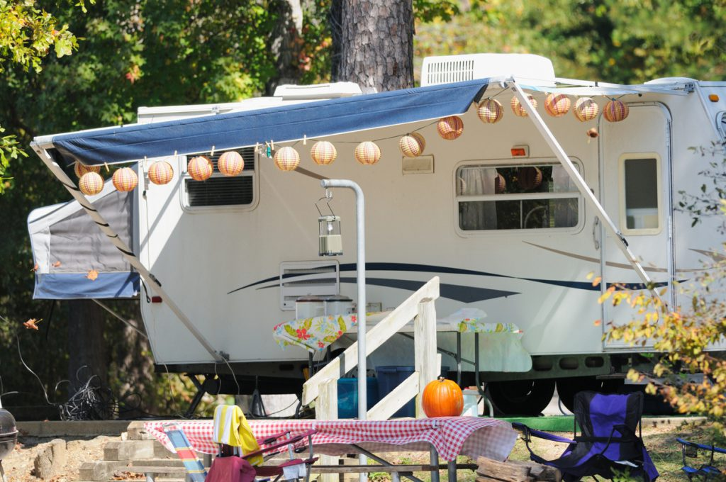 """""""Hybrid travel trailer with pop outs in campground during autumn, horizontal."""""""
