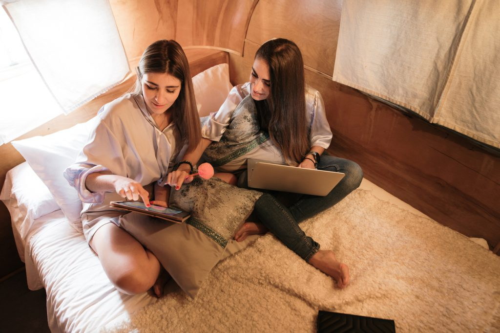 RV wifi - Two young women sitting on a vintage motor home bed. They are using technology: a laptop and a digital tablet