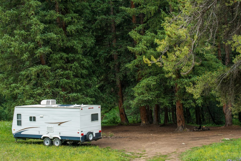 Boondocking Dry Camping in the Forest. Small Travel Trailer with Solar Panels on Roof.