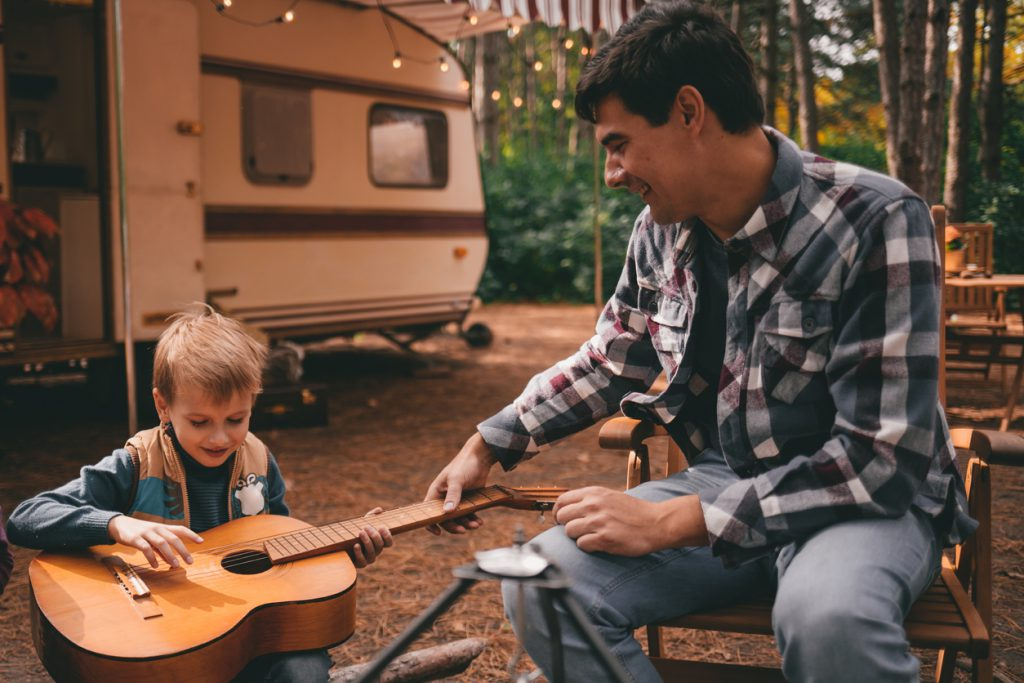 RV myths busted - Father teaches son play guitar on camping trip relaxing in the autumn forest. Camper trailer. Fall season outdoors trip