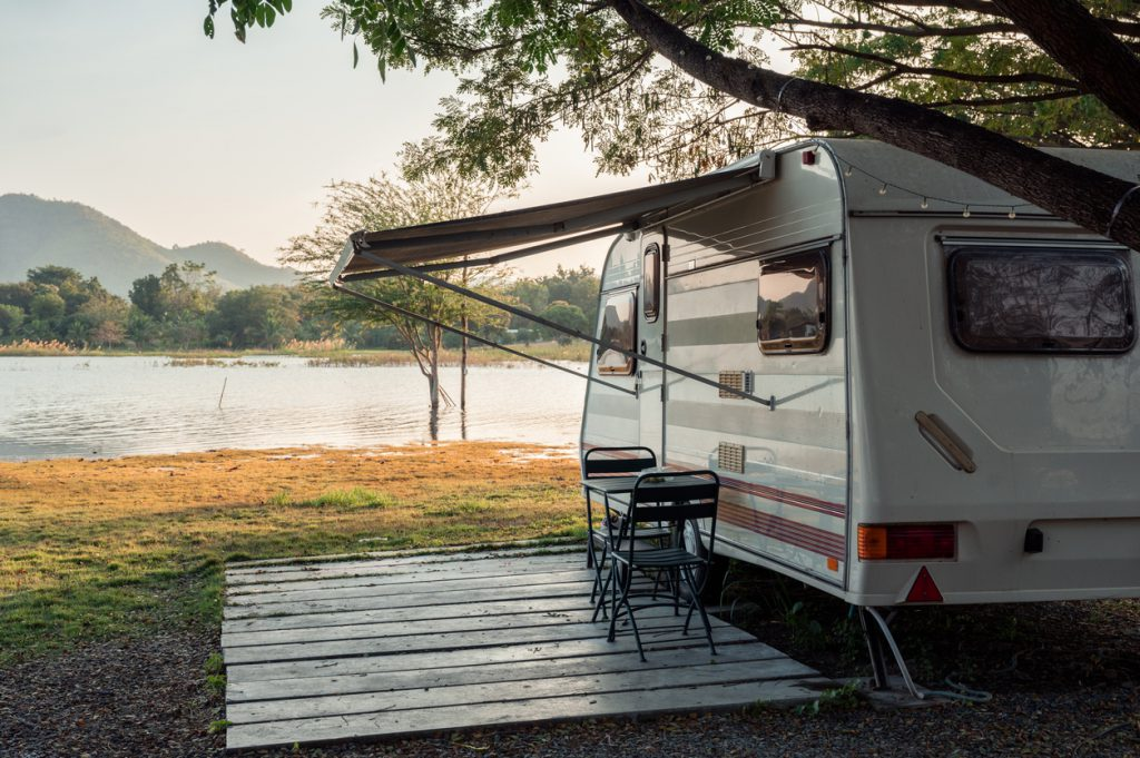 Motor home parked near lakeside in campground at evening on vacation trip